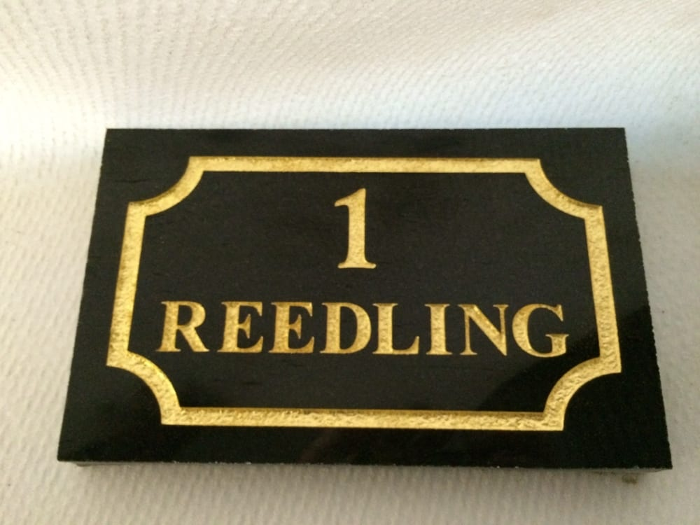 Black granite house plaque with gold lettering reading reedling