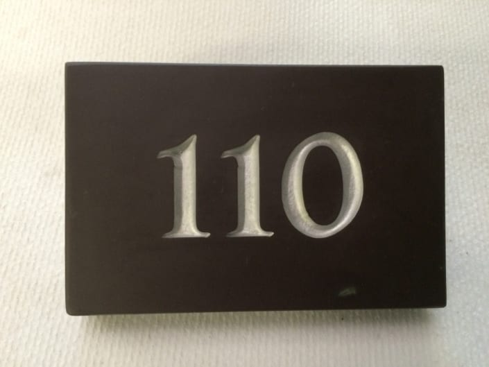 number 110 house plaque with silver lettering